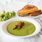 Green soup in a bowl with homemade croutons. Whole green grape tomatoes and grilled cheese sandwich on plate in background. Text overlay: Garlic Roasted Green Tomato Soup.
