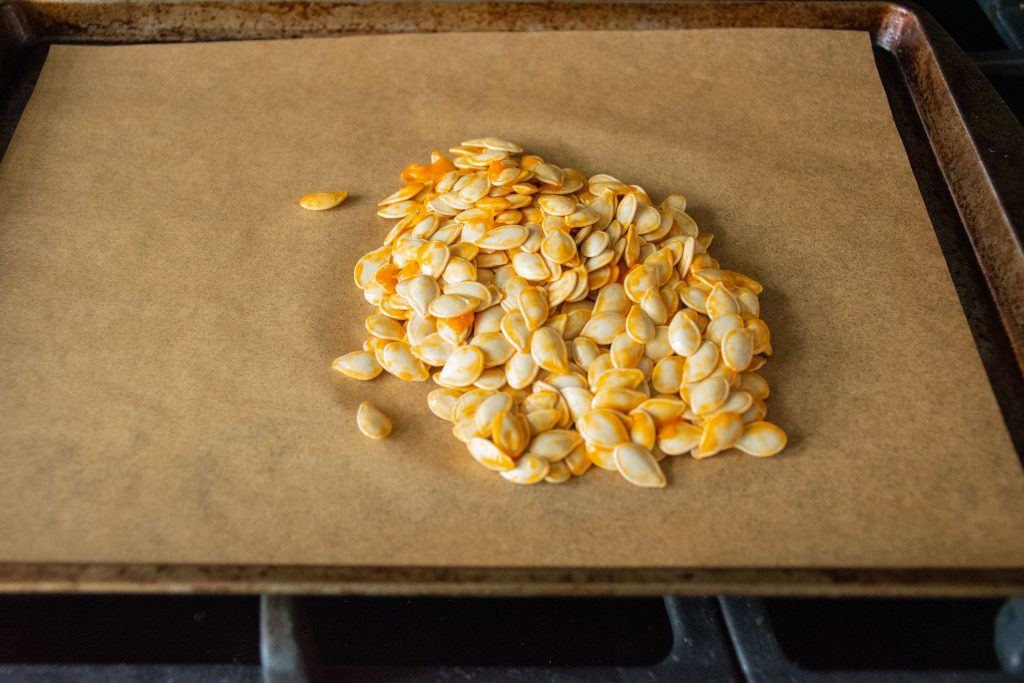 Raw pumpkin seeds in a pile on a baking sheet.