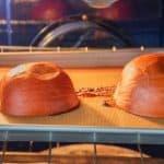 2 pie pumpkin halves face down on baking sheet after baking.