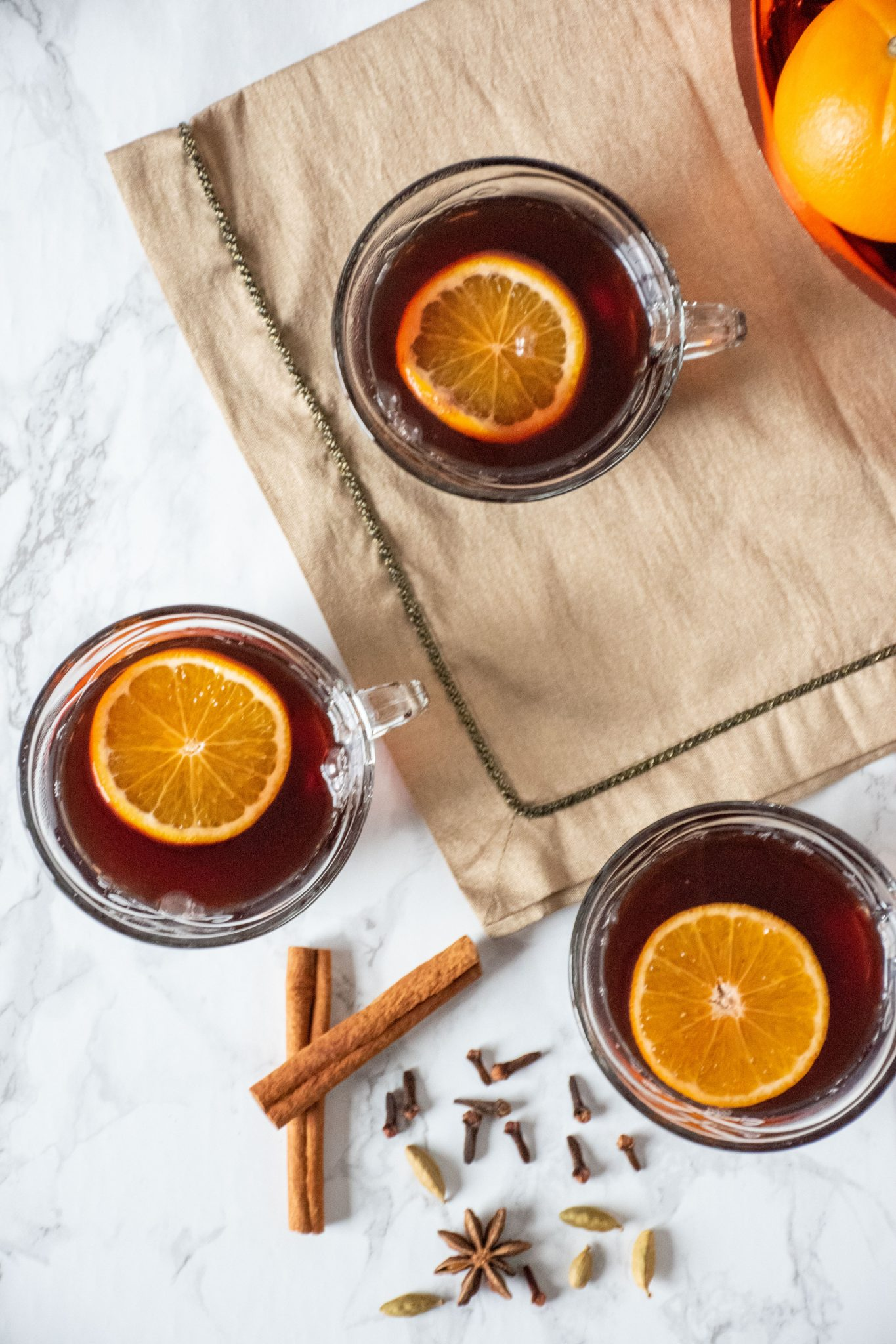 Overhead shot of 3 small glass mugs filled with mulled grape juice, each with an orange slice in them.
