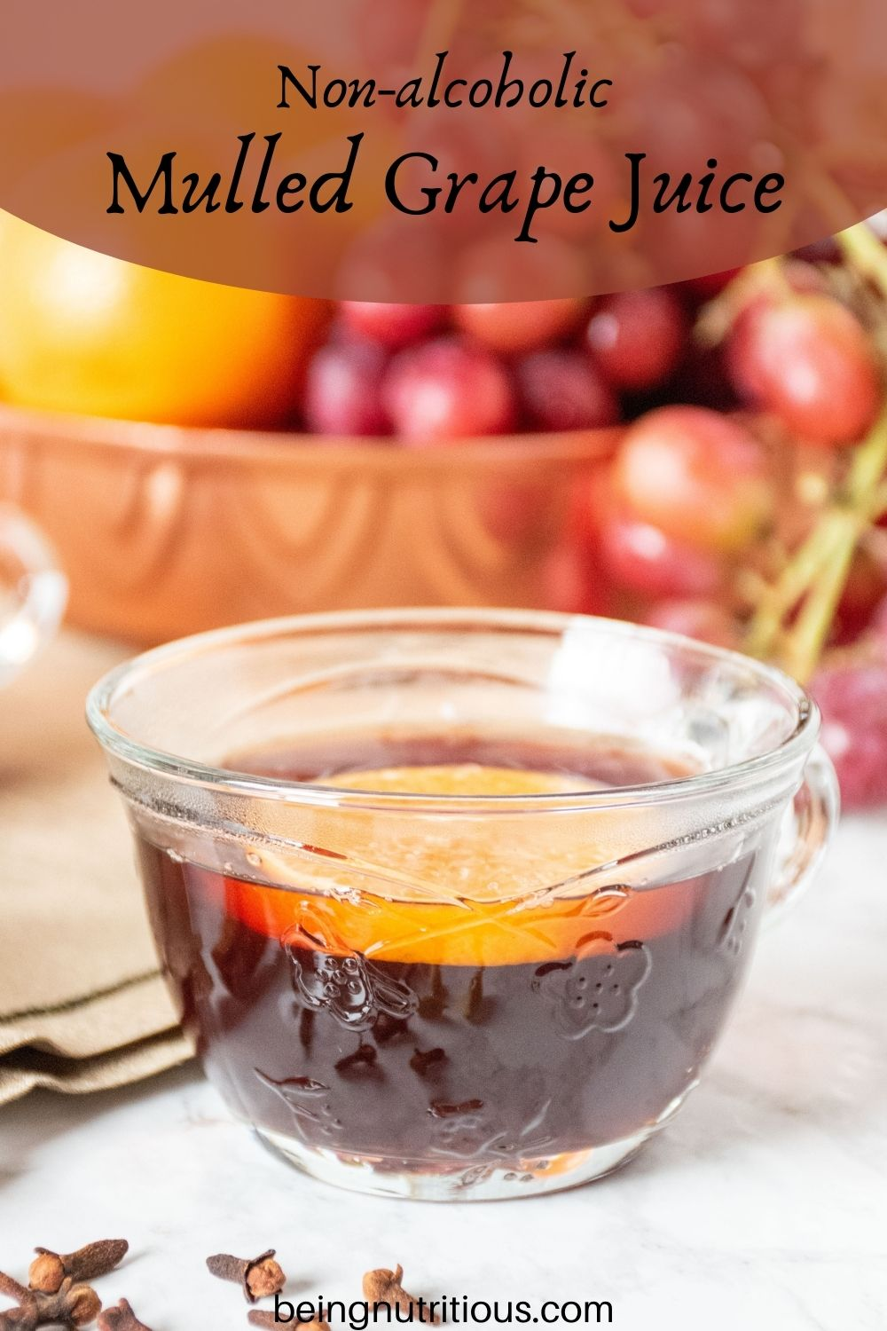 Close up of a small glass mug, filled with mulled grape juice, with an orange slice in it. Text overlay: non-alcoholic mulled grape juice.