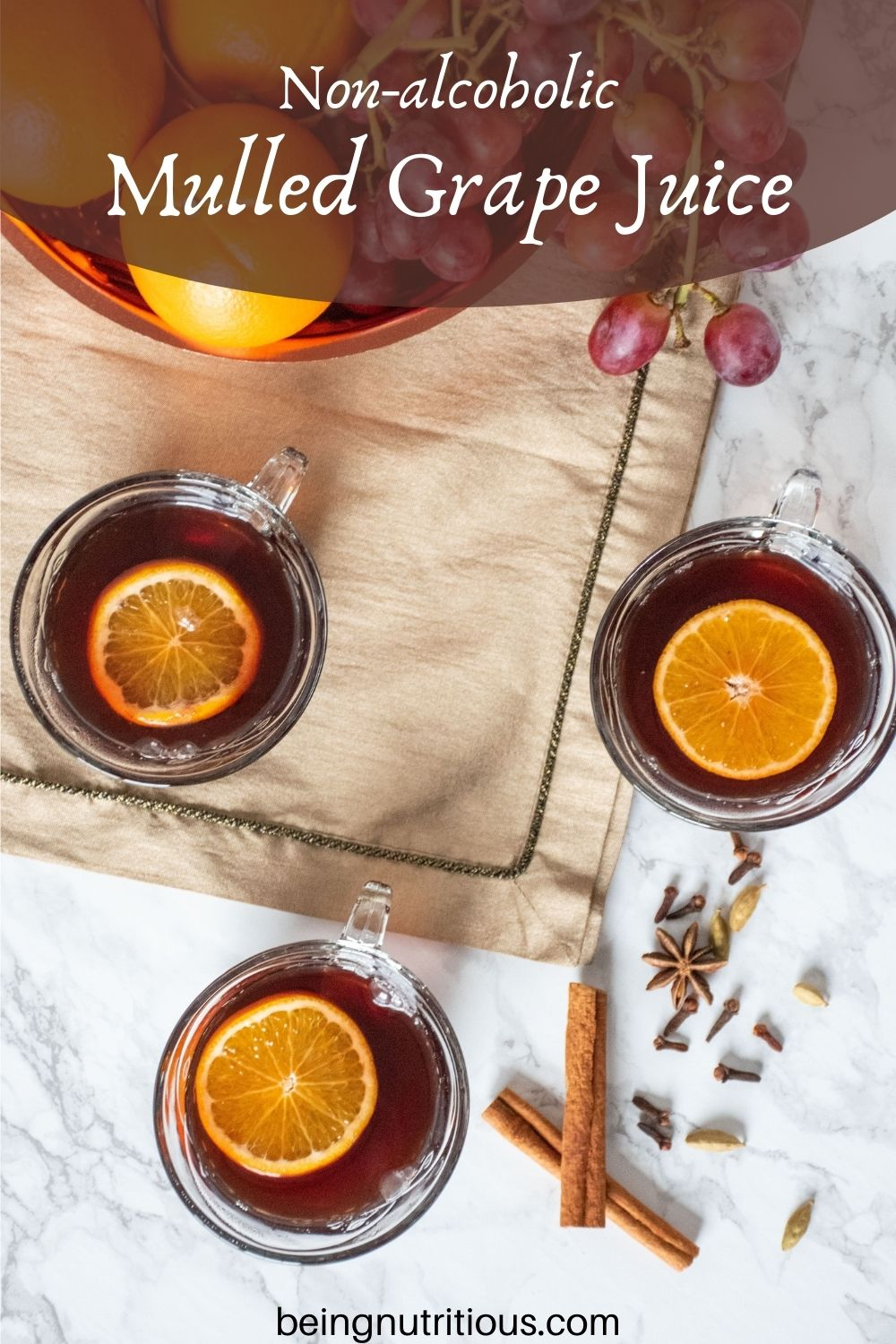 Overhead shot of 3 small glass mugs filled with mulled grape juice, each with an orange slice in them. Text overlay: Non-alcoholic Mulled Grape Juice.