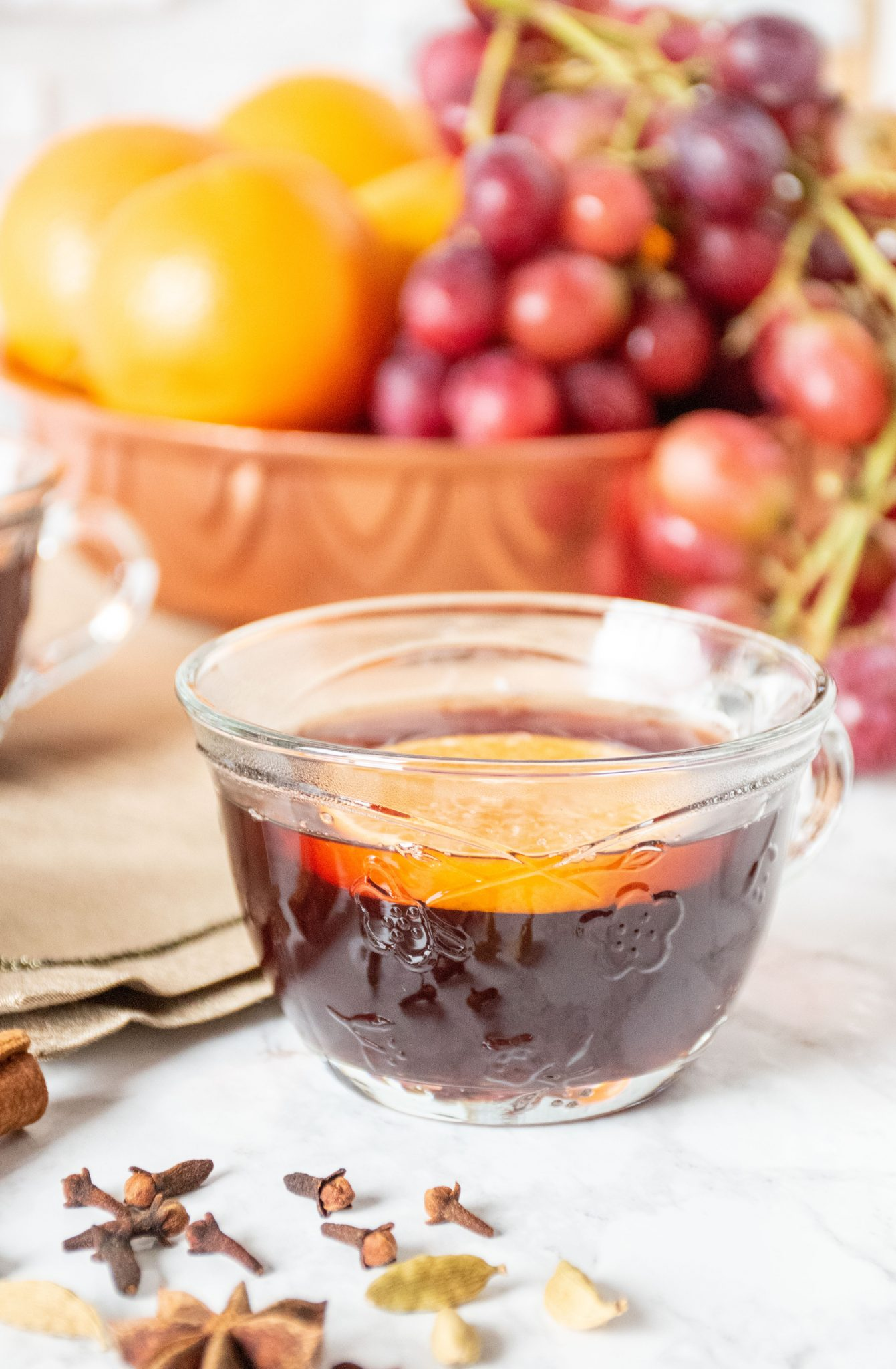 Close up of a small glass mug, filled with mulled grape juice, with an orange slice in it.