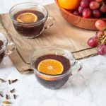 Small glass mugs filled with mulled grape juice, each with a slice of orange in them. Fresh grapes and oranges in background.