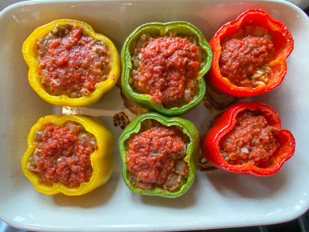 Baked stuffed peppers in a baking pan.