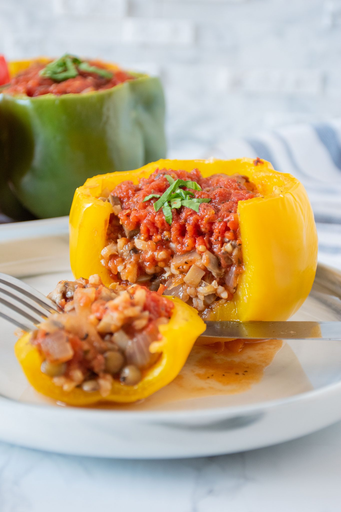 A yellow stuffed pepper, side cut open to reveal stuffing, on a plate.