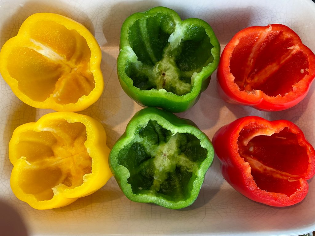 Six bell peppers in a prepared baking pan.