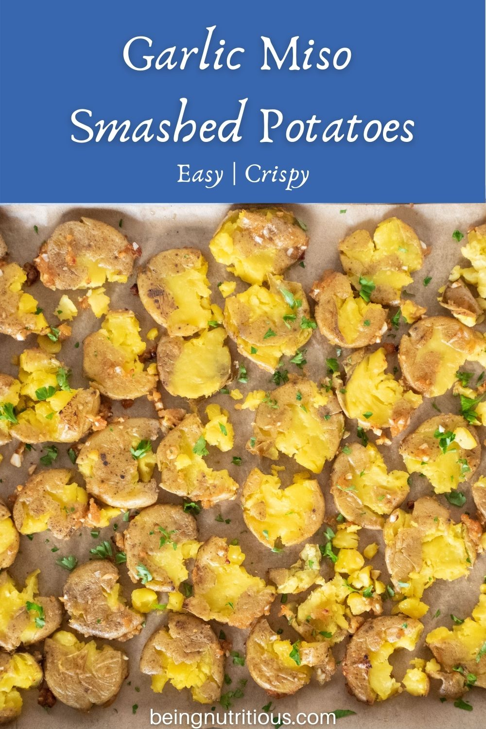 Overhead picture of smashed potatoes on a baking sheet. Text overlay: Garlic Miso Smashed Potatoes; easy, crispy.