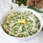 Bowl of mashed potatoes with a pat of butter on top. Text overlay: Healthy Colcannon (Irish mashed potatoes with kale).