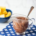 Chocolate sauce in a small glass pitcher, with a bowl of pineapple chunks in background.