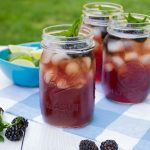 Iced tea in Mason jars, with ice, blackberries, and mint.
